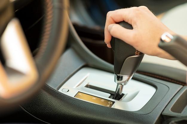 Zamyka up kobieta kierowca trzyma jej rękę na automatycznej zmiany biegów kija jeżdżeniu jako samochód.
