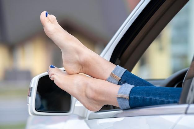 Zamyka up kobieta kierowcy bose stopy wtyka z samochodowego otwartego okno.