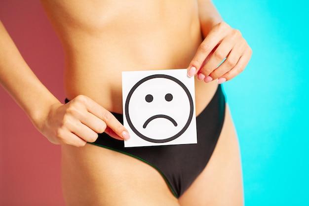 Zamyka up kobieta ma żeńskich problemy zdrowotne trzyma kartę z smutnym uśmiechem