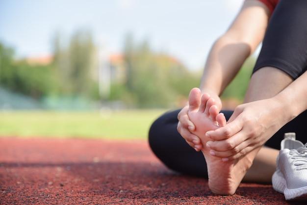 Zamyka up kobieta masuje jej nożnego ból na podłoga po biegać.