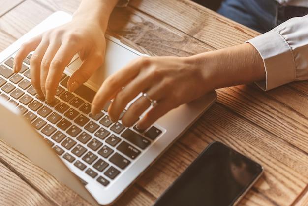 Zamyka up kobieta pisać na maszynie na laptopie w sklep z kawą