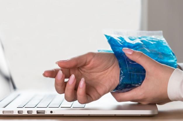 Zamyka up kobieta stosuje zimnego kompres jej bolesny nadgarstek spowodowany przedłużającą się pracą na komputerze, laptop. zespół cieśni nadgarstka