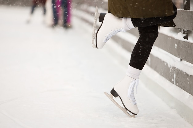 Zamyka up kobiety łyżwiarki nogi przy otwartym łyżwiarskim lodowiskiem, boczny widok. kobiece białe łyżwy na lodzie, pociągi przy ścianie, uczenie się równowagi. zajęcia weekendowe na zewnątrz w chłodne dni.