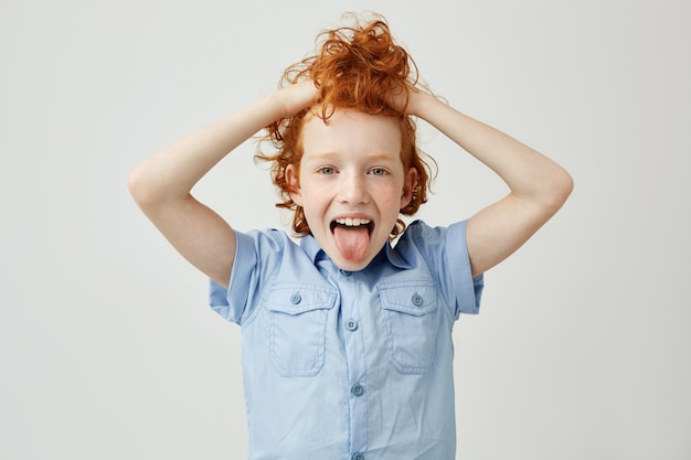Zamyka up ładne dziecko z pomarańczowym kędzierzawym włosy i piegami trzyma włosy z rękami, pokazuje język, robi niemądremu wyrazowi twarzy
