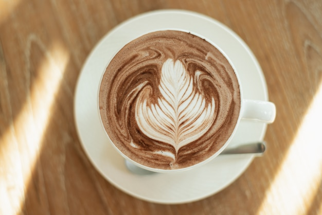 Zamyka up latte sztuki gorąca kawa na drewno stole