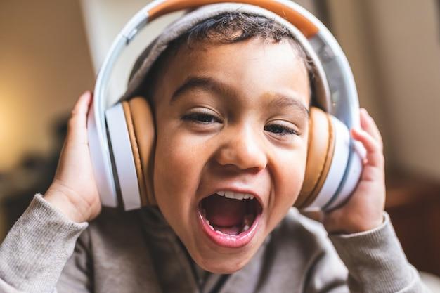 Zamyka up latyno-amerykański chłopiec słuchająca muzyka na hełmofonach.