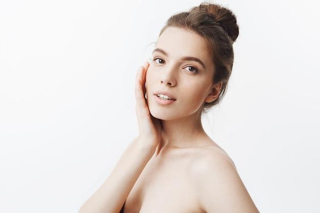 Zamyka up lodowa atrakcyjna caucasian młoda studencka dziewczyna z brown włosy w modnej babeczki fryzury mienia twarzy z ręką w trzy cytatach z zrelaksowanym i zachwytem wyraża twarz.