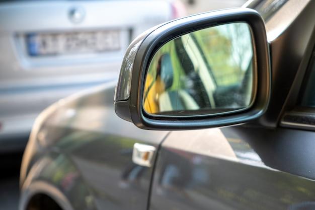 Zamyka up lusterko wsteczne samochód parkujący blisko krawężnika na stronie ulicy na parkingu.
