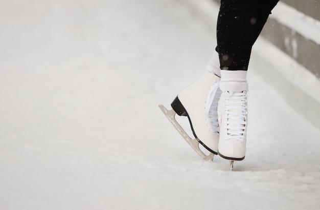 Zamyka up łyżwiarki nogi przy otwartym łyżwiarskim lodowiskiem, dolny widok. kobiece białe łyżwy na lodzie, pociągi przy ścianie, uczenie się równowagi