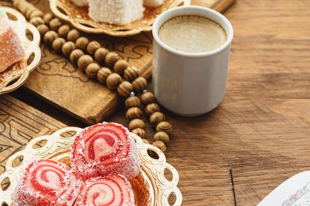 Zamyka up mały talerz z tureckimi cukierkami i filiżanką kawa espresso na drewnianym stole