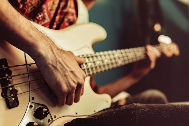 Zamyka up męska ręka bawić się gitarę elektryczną w zmroku