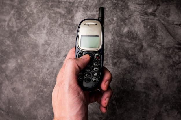 Zamyka up męska ręki prasa na guziku przestarzały telefon komórkowy.