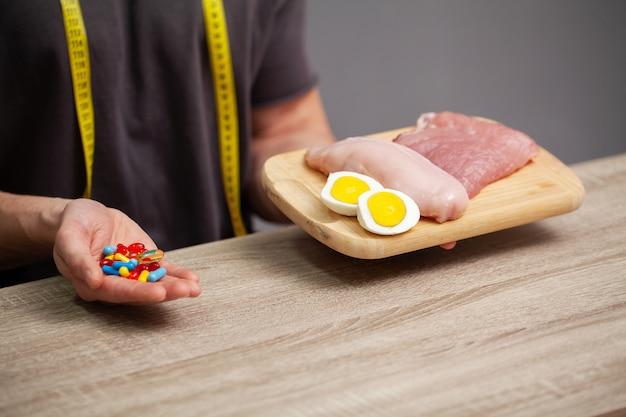 Zamyka up męskie ręki z jedzeniem bogatym w proteinę na tnącej desce i pigułkę na stole