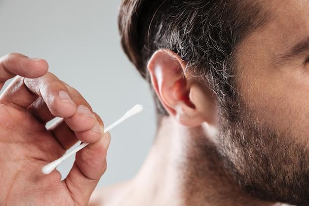 Zamyka up mężczyzna czyści jego ucho