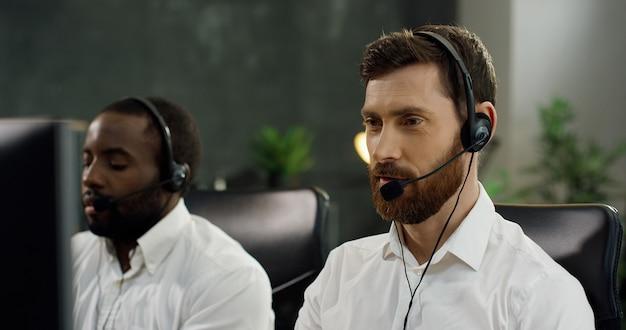 Zamyka up mężczyzna gawędzi z klientem przy komputerem i rozwiązuje problem w słuchawki, amerykanina afrykańskiego pochodzenia współpracownik na tle