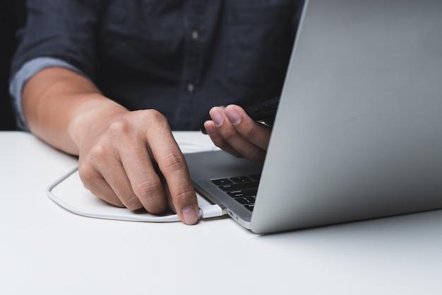 Zamyka up mężczyzna ładuje telefon komórkowego z laptopem