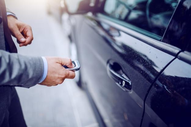 Zamyka up mężczyzna otwiera jego samochód na dżdżystej pogodzie.