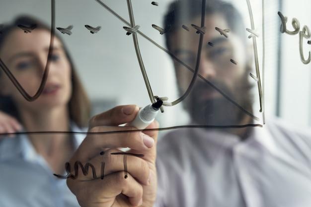 Zamyka up mężczyzna wyjaśnia biznesowe analityka jego żeński kolega z wykresem na whiteboard