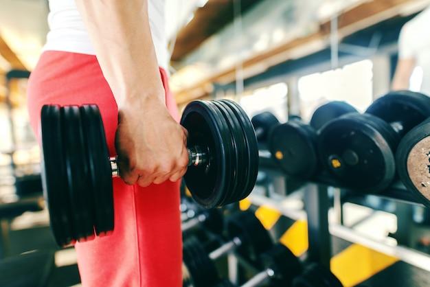 Zamyka up mężczyzna zrywania dumbbell podczas gdy stojący w gym.