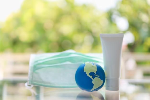 Zamyka up mini światowa piłka z chirurgicznie twarzy maską i butelka alkoholu gel sanitizer z zielonym natury tłem.