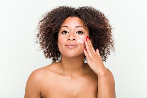 Zamyka up młoda amerykanin afrykańskiego pochodzenia kobieta stosuje nawilżanie śmietankę