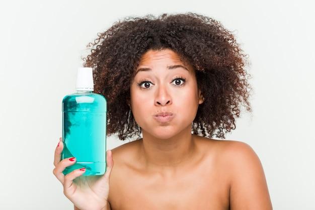 Zamyka up młoda amerykanin afrykańskiego pochodzenia kobieta trzyma płukankę do ust
