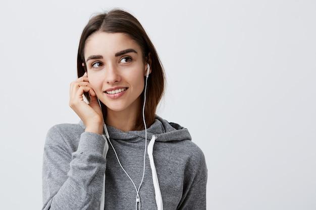 Zamyka up młoda atrakcyjna rozochocona caucasian kobieta z ciemnymi włosy w przypadkowej szarej bluzie z kapturem ono uśmiecha się jaskrawy, trzyma słuchawki z ręką, patrzeje na boku z marzycielskim i radosnym wyrazem twarzy.