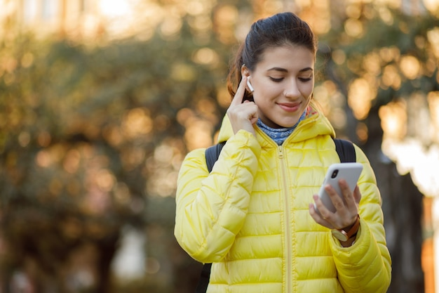 Zamyka up młoda brunetki kobieta z nowożytnymi bezprzewodowymi słuchawkami i używać jej telefonu komórkowego odprowadzenie przy miasto ulicą