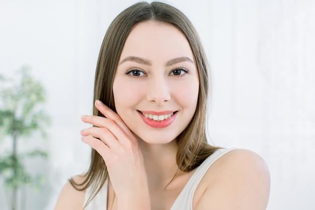 Zamyka up młoda kaukaska piękna kobieta z smiley twarzą. portret rozochocona atrakcyjna młoda kobieta patrzeje kamerę z radością. na białym tle koncepcja pielęgnacji włosów i naturalnego piękna