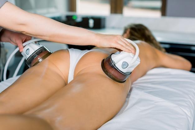 Zamyka up młoda kobieta dostaje próżniowego ciało masaż problematyczne obszary na udzie i pośladkach z profesjonalnym wyposażeniem.