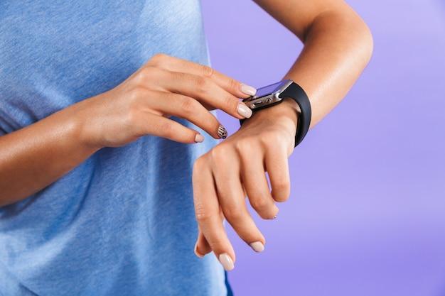 Zamyka up młoda kobieta dotyka jej smartwatch