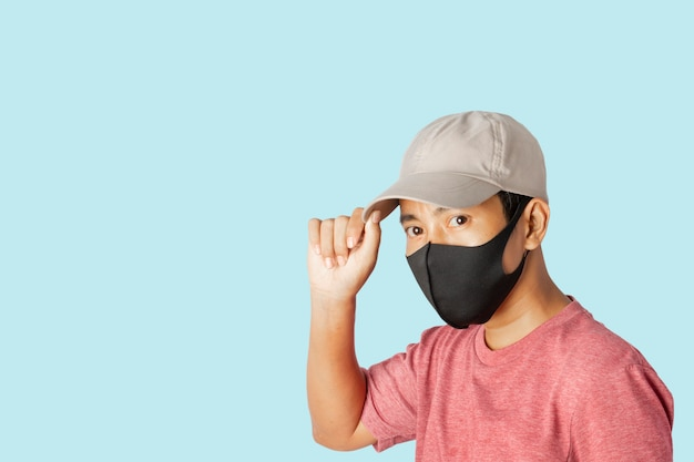 Zamyka up młoda samiec jest ubranym ochronną twarzy maskę na błękitnym tle.