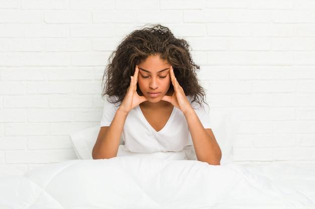 Zamyka up młodego amerykanina afrykańskiego pochodzenia kobiety zmęczony obsiadanie na łóżku