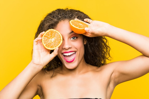 Zamyka up młodego amerykanina afrykańskiego pochodzenia piękna i makijaż kobieta trzyma grapefruitowego