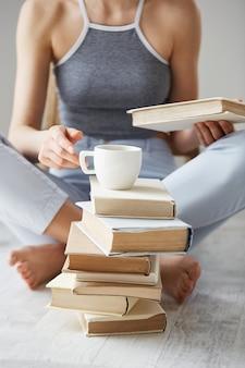 Zamyka up młodej kobiety mienia książki i filiżanki obsiadanie na podłoga nad biel ścianą wcześnie w ranku.