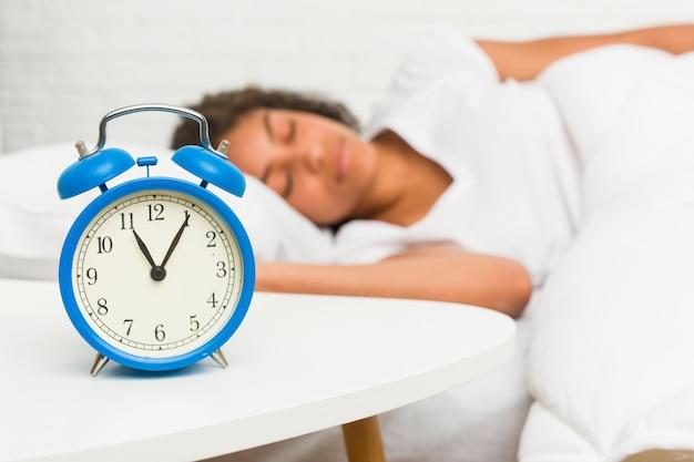 Zamyka up młody amerykanin afrykańskiego pochodzenia kobiety dosypianie na łóżku