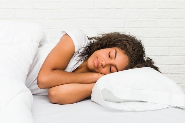 Zamyka up młody amerykanin afrykańskiego pochodzenia kobiety zmęczony dosypianie na łóżku