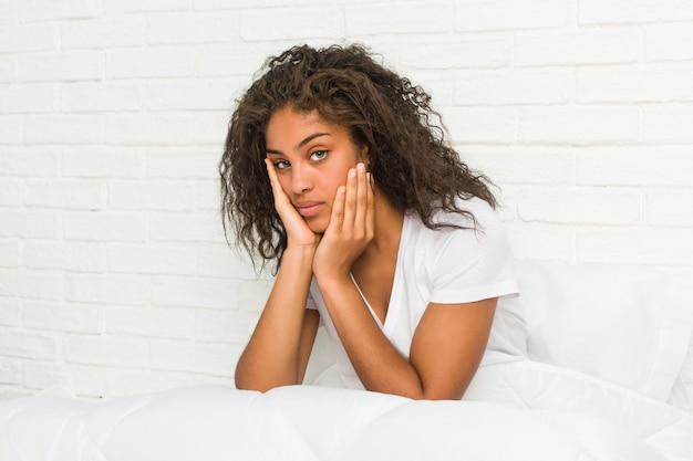 Zamyka up młody amerykanin afrykańskiego pochodzenia kobiety zmęczony obsiadanie na łóżku