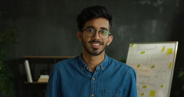 Zamyka up młody arabski przystojny facet w niebieskich dżinsach koszula i szkłach stoi w biurze, obraca głowę kamera i ono uśmiecha się.