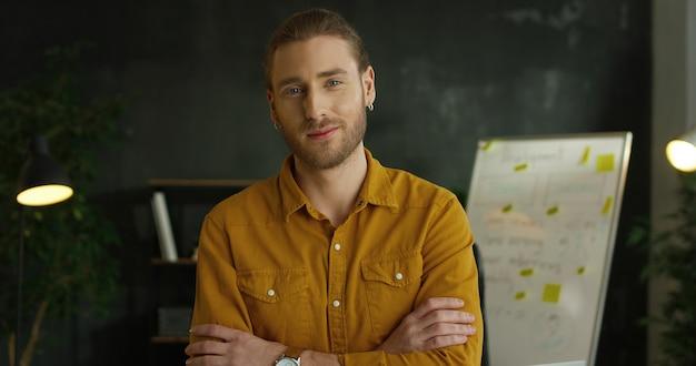 Zamyka up młody przystojny mężczyzna w żółtej koszulowej pozyci w biurowym pokoju i patrzeć kamerę z poważną twarzą.