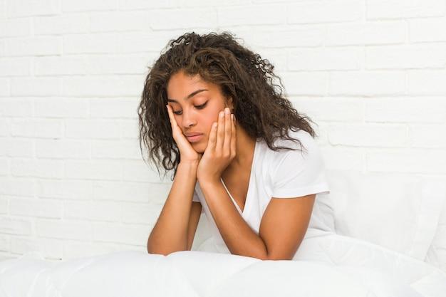 Zamyka up młody zmęczony kobiety obsiadanie na łóżku