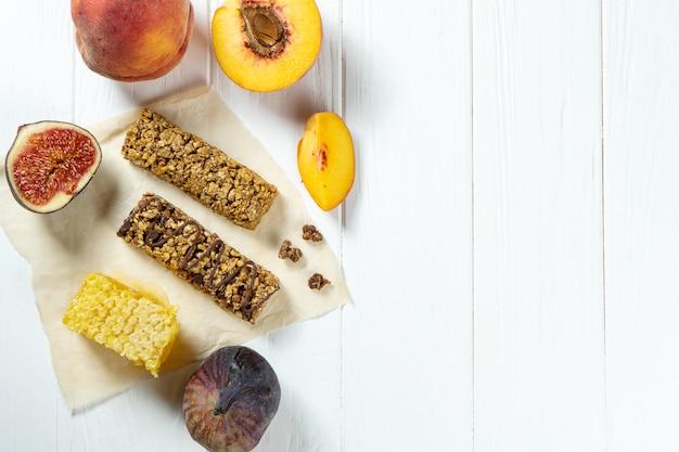 Zamyka up na granola barze z honeycombs i figami, brzoskwinia na rzemiosło papierze na białym drewnianym tle.