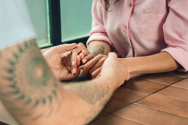 Zamyka up na mężczyzna i kobiecie trzyma ręki przy drewnianym stołem
