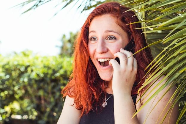 Zamyka up niespodzianki dziewczyna opowiada na telefonie komórkowym z rudzielec podczas gdy stojący outdoors