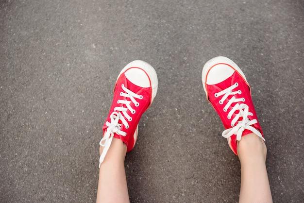 Zamyka up nogi w czerwonych keds kłama na asfalcie.