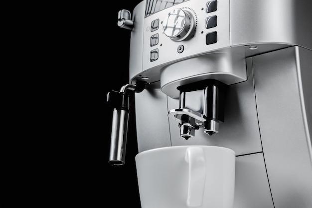 Zamyka up nowożytna kawowa maszyna i biała filiżanka przy czarnym tłem
