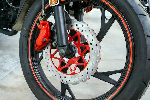 Zamyka up nowożytny czerwony motocyklu hamulca tło
