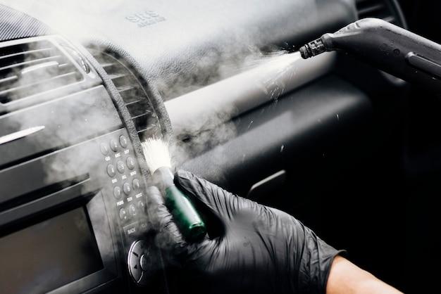 Zamyka up osoby cleaning samochodu wnętrze