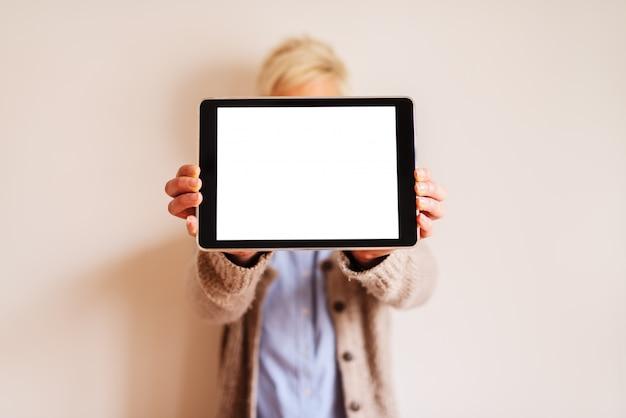 Zamyka up ostrość widok pastylka z białym editable ekranem. zamazany obraz kobiety stojącej za tabletem i trzymającej go.