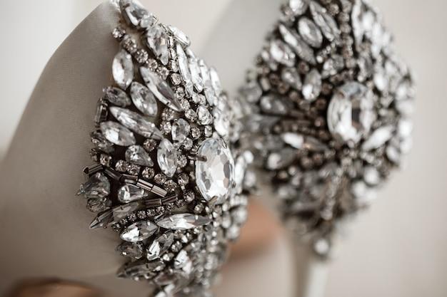 Zamyka up panna młoda buty z biżuterią. poranek panny młodej. stylowe buty ślubne z klejnotami. koncepcja ślubu. luksusowe nowoczesne wysokie wzgórza dla panny młodej. koncepcja ślubu